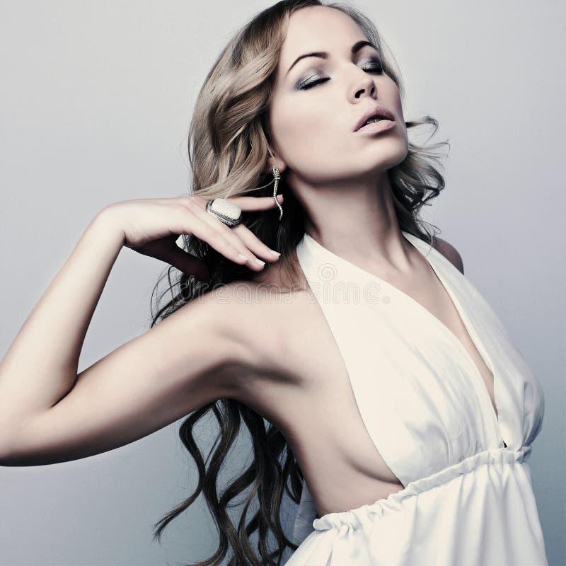 Schöne elegante blonde Frau im weißen Kleid stockfoto