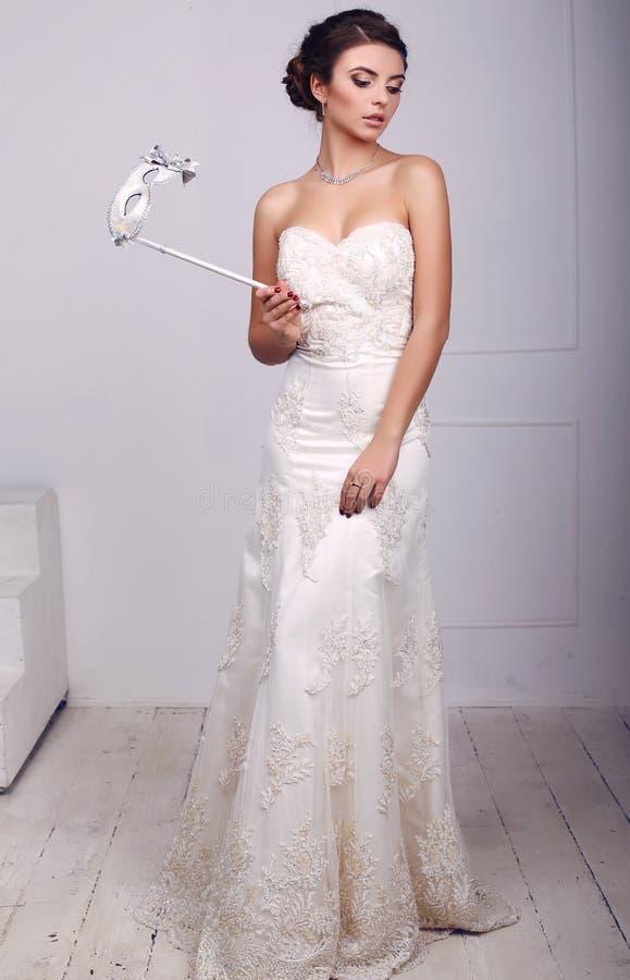 Schöne elegante Braut im Hochzeitskleid mit Maske in den Händen, stockbild