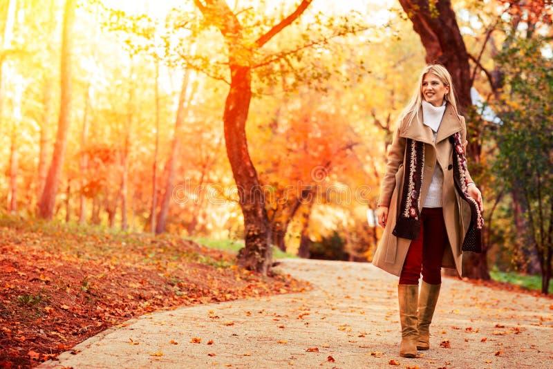 Schöne elegante Frau, die durch den a-Herbstpark geht lizenzfreie stockfotografie