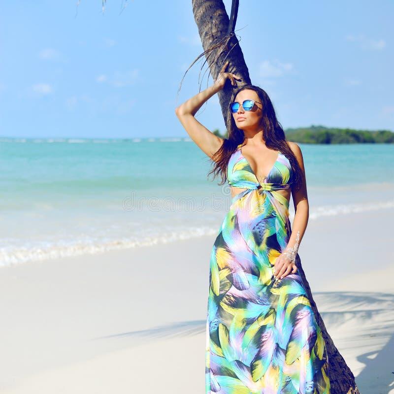 Schöne elegante Frau, die nahe Palme auf einem Strand aufwirft lizenzfreie stockbilder