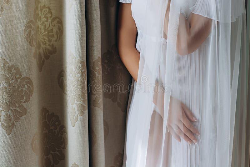 Schöne elegante Hände der Braut unter dem Schleier stockfoto