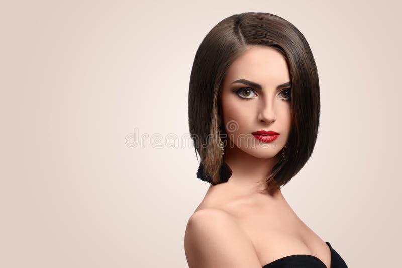 Schöne elegante junge Frau, die im Studio aufwirft lizenzfreie stockbilder