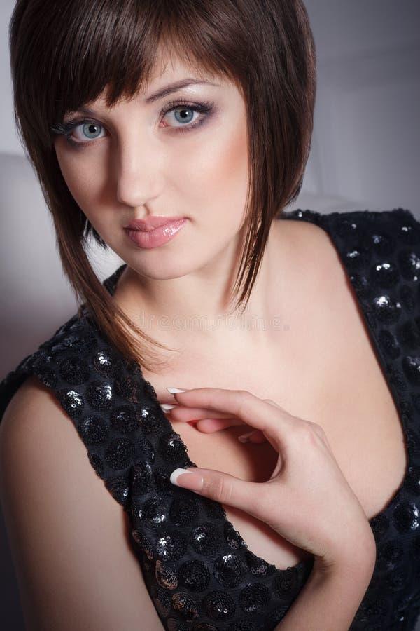 Schöne elegante junge Frau, die schwarzes Kleid trägt lizenzfreies stockbild