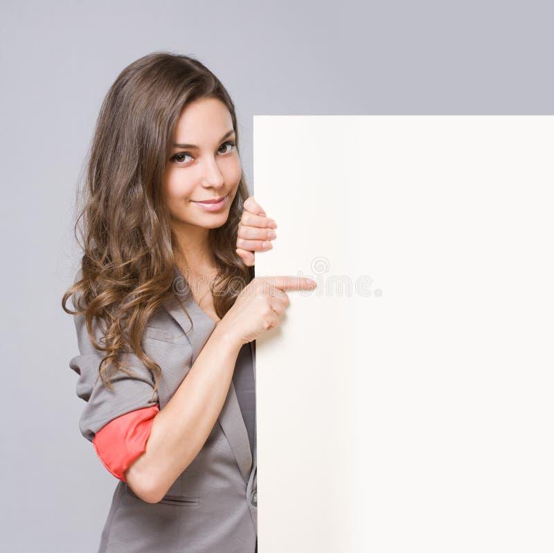 Elegante junge Geschäftsfrau mit leerem weißem Zeichen. lizenzfreie stockfotos