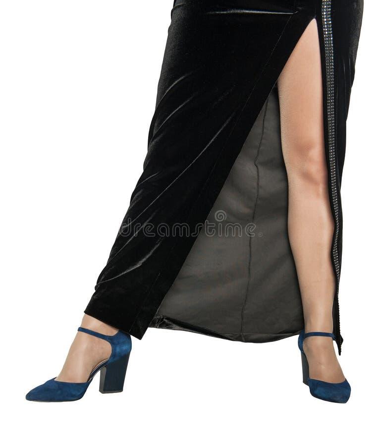 Schöne Eleganzfrauenbeine in den blauen Schuhen und schwarzen im Kleid lokalisiert lizenzfreie stockfotografie