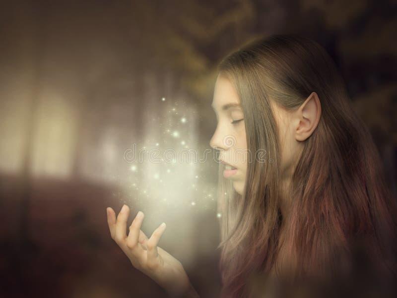 Schöne Elfenmädchen-Porträtnahaufnahme im Wald, der das Glühen auf ihrer Hand betrachtet Fantasiefotokunst stockbilder