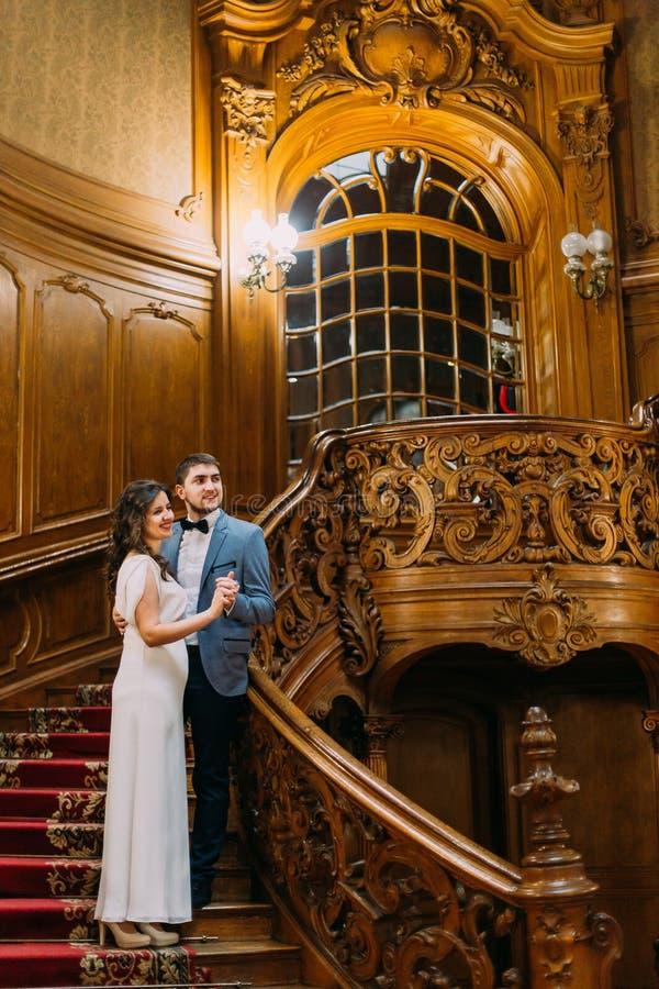 Schöne empfindliche Braut und hübscher eleganter Bräutigam, die auf alter Treppe mit dem Hintergrund von herrlichem hölzernem umf stockfoto