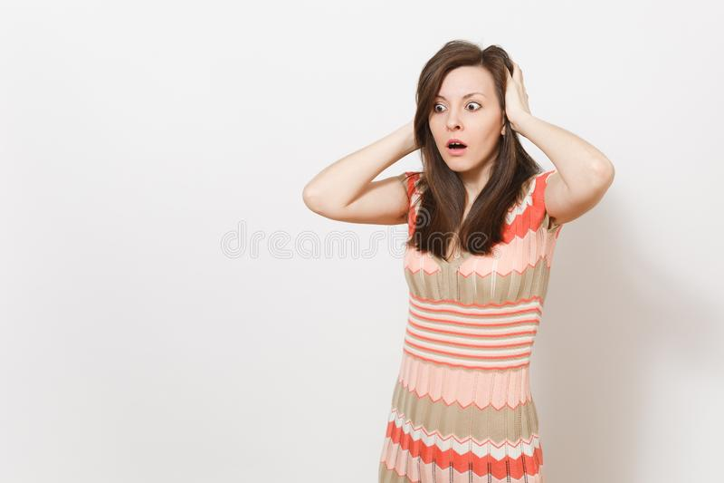 Schöne entsetzt stören junges brunette Mädchen in hellem Beige und rosa kopiertes Kleid hält ihre Hände nahe Kopf herein stockfotografie