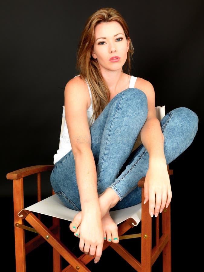 Schöne entspannte besorgte durchdachte junge Frau, die in einem Stuhl sitzt lizenzfreie stockbilder
