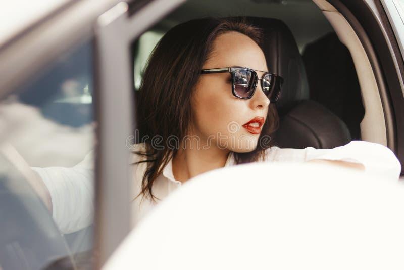 Schöne erfolgreiche elegante brunette junge Frau mit den roten Lippen in der Sonnenbrille, die Personenkraftwagen fährt lizenzfreies stockfoto