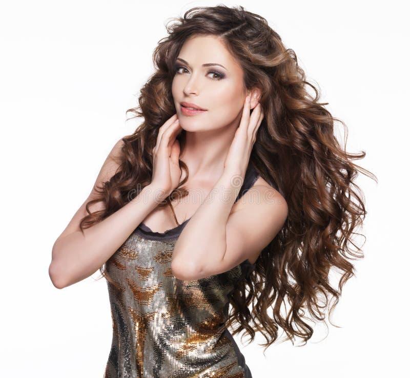 Schöne erwachsene Frau mit dem langen braunen gelockten Haar. stockfoto