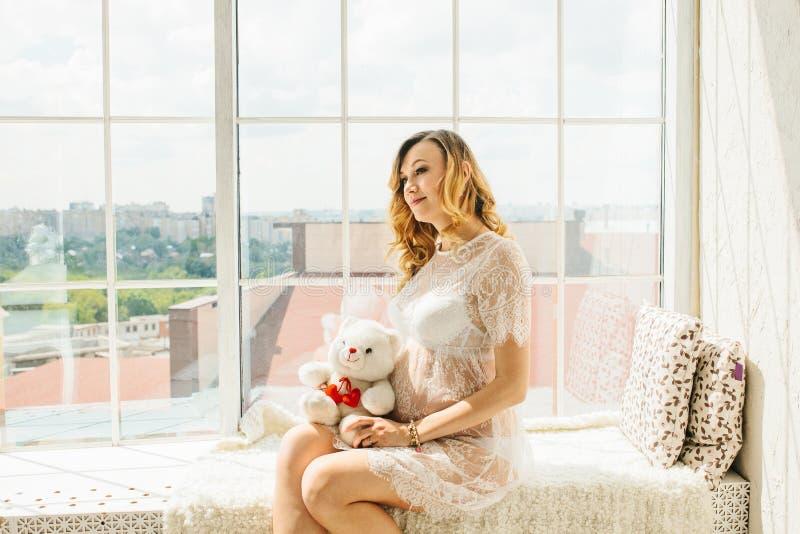 Schöne erwachsene schwangere Frau Aufwartung des Schätzchens Schwangerschaft Sorgfalt, Weichheit, Mutterschaft, Geburt stockfotos