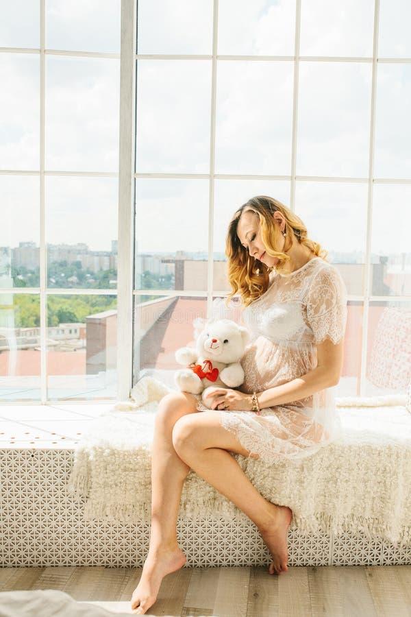 Schöne erwachsene schwangere Frau Aufwartung des Schätzchens Schwangerschaft Sorgfalt, Weichheit, Mutterschaft, Geburt stockfoto