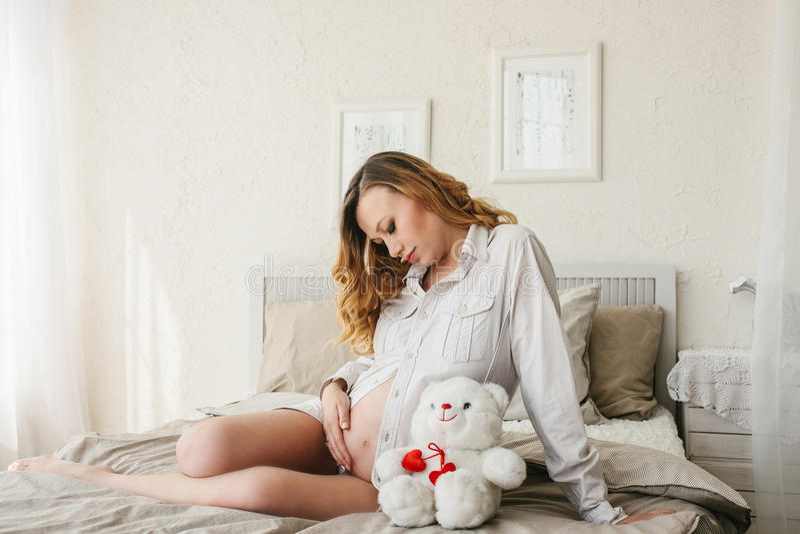 Schöne erwachsene schwangere Frau Aufwartung des Schätzchens Schwangerschaft Sorgfalt, Weichheit, Mutterschaft, Geburt stockbilder
