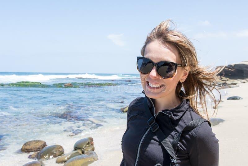 Schöne erwachsene weibliche Haltungen an La- Jollastrand in San Diego, tragende Sonnenbrille stockfotos