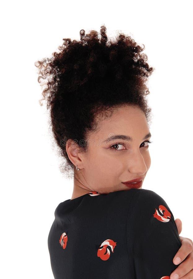 Schöne ethnisch gemischte Frau, die über ihrer Schulter schaut stockbilder