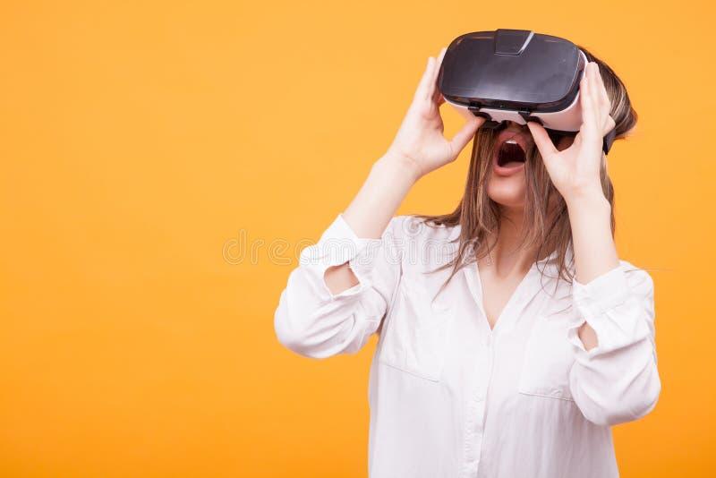 Schöne experimentierende Schutzbrillen der virtuellen Realität des jungen Mädchens über gelbem Hintergrund stockfotos