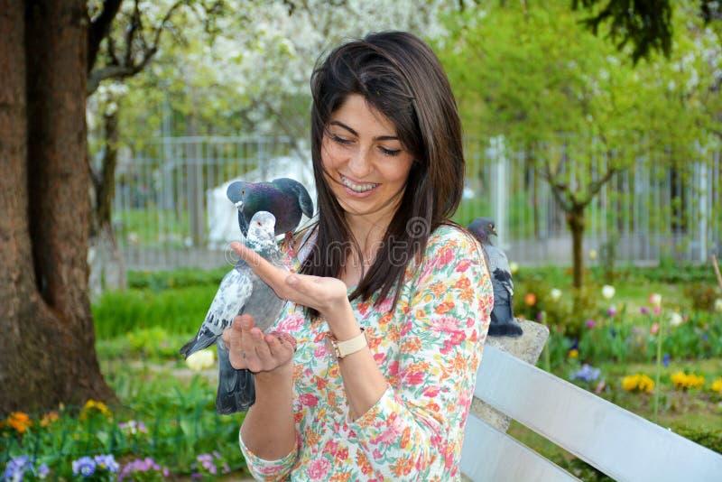 Schöne Fütterungstauben der jungen Frau in einem Frühlingsgarten stockbilder