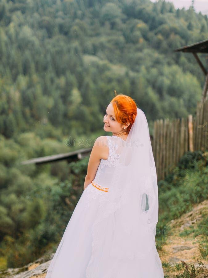 Schöne fabelhafte glückliche redhair Braut, die auf dem Hintergrund von Karpaten-Bergen aufwirft stockfoto