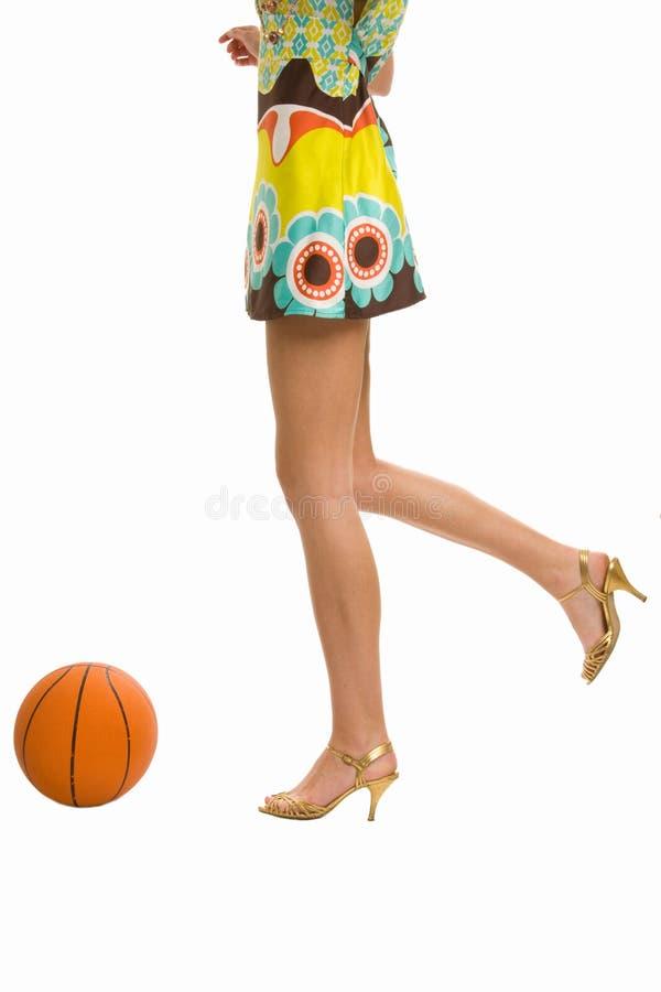 Schöne Fahrwerkbeine auf hohen Absätzen mit Basketball lizenzfreies stockbild