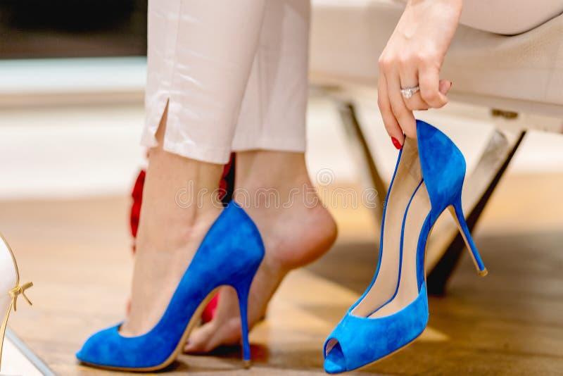 Schöne Fahrwerkbeine Frau, die viele Schuhe versucht wählen stockbilder