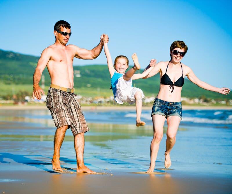 schöne Familie auf dem Strand lizenzfreie stockfotos