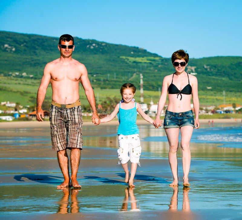 schöne Familie auf dem Strand lizenzfreie stockbilder