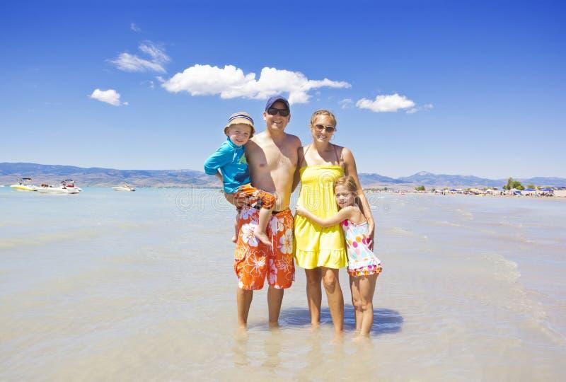 Schöne Familie, die am Strand spielt lizenzfreies stockbild