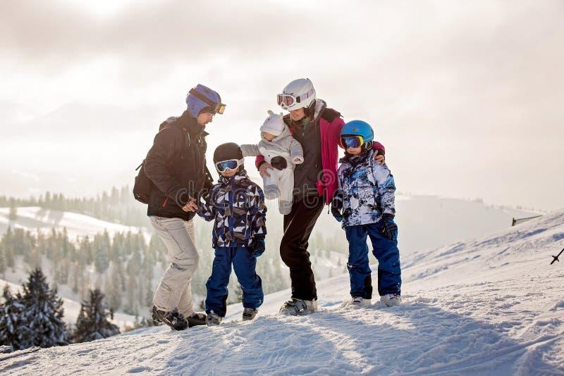 Schöne Familie mit den Kindern, fahrend in einem Landschaftsbereich auf Österreicher Ski stockbild