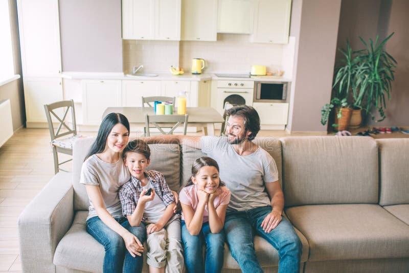 Schöne Familie sitzt auf Sofa in der Küche Sie verbringen Zeit zusammen Kerllächeln und -blicke auf Frau Junge lehnt sich lizenzfreies stockfoto
