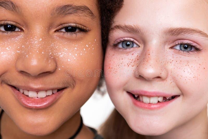 Schöne fehlerlose Kinder, die bei der Aufstellung vollständig unterschiedlich schauen stockbilder