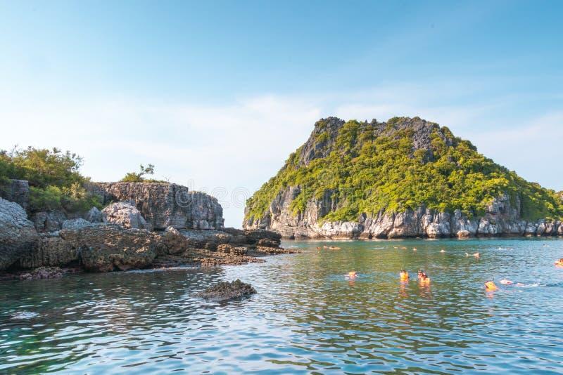 Schöne Felsen mit Vegetation und Schwimmern schwimmen im Meer unter blauen Himmel stockfotos