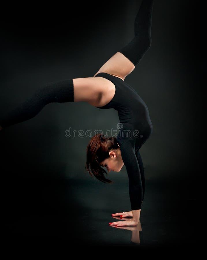 Schöne flexible junge Turnerathletenfrau im schwarzen Trikotanzug lizenzfreie stockfotografie