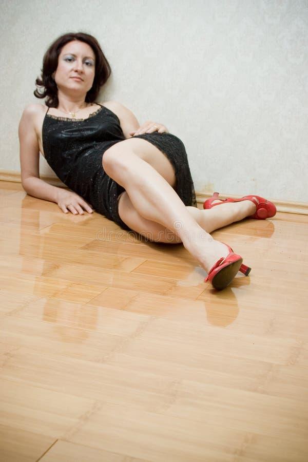 Schöne Frau auf dem Fußboden stockbild