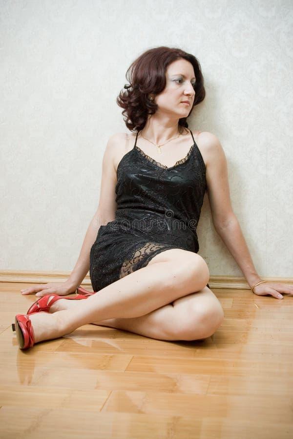 Schöne Frau auf dem Fußboden lizenzfreie stockbilder