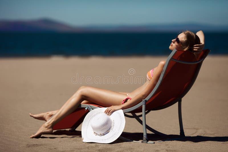 Schöne Frau auf einem deckchair am Strand lizenzfreie stockbilder