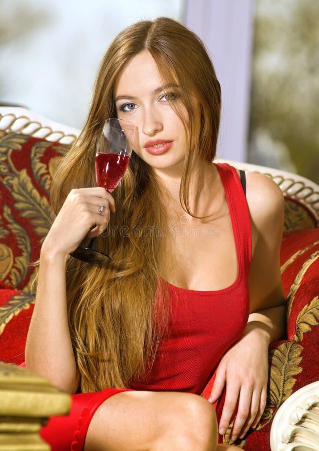 Schöne Frau auf einem Sofa mit Glas lizenzfreie stockbilder