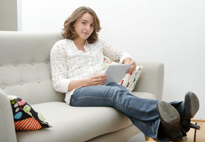 Schöne Frau der jungen Frau mit einer Tablette im Sofa lizenzfreie stockfotografie