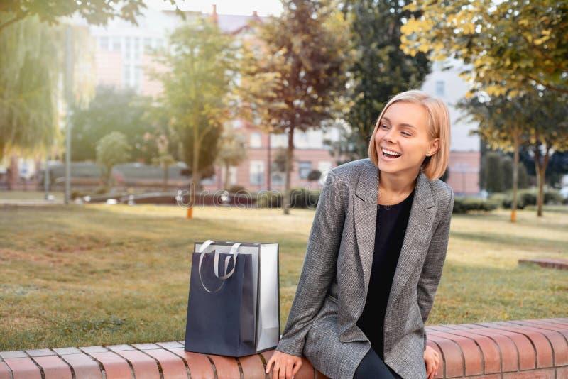 Schöne Frau in der Stadt mit Einkaufstaschen stockfotografie