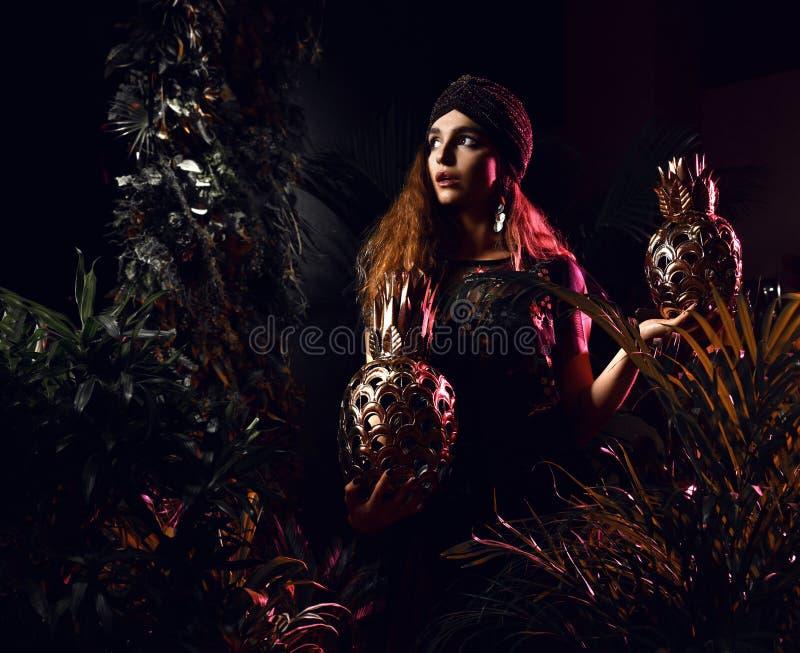 Schöne Frau des gelockten Haares der Mode, die im grünen Kleid im tropischen Blattwald mit großen Goldananasfrüchten aufwirft stockfotos