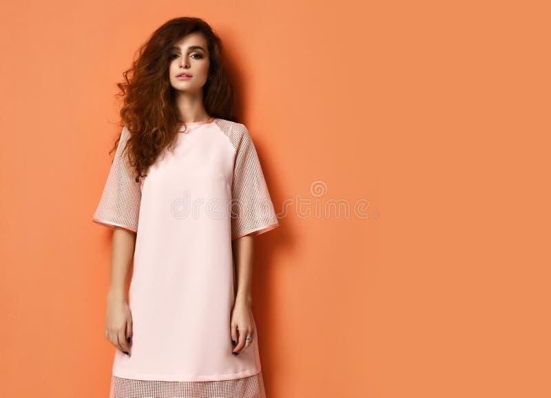 Schöne Frau des gelockten Haares im Pastellfarbrosakleid, das auf Orange steht stockfotos