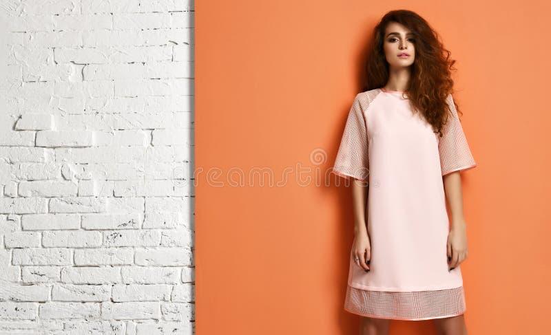Schöne Frau des gelockten Haares im Pastellfarbrosakleid, das auf Orange und Backsteinmauer mit Textraum steht stockfotos