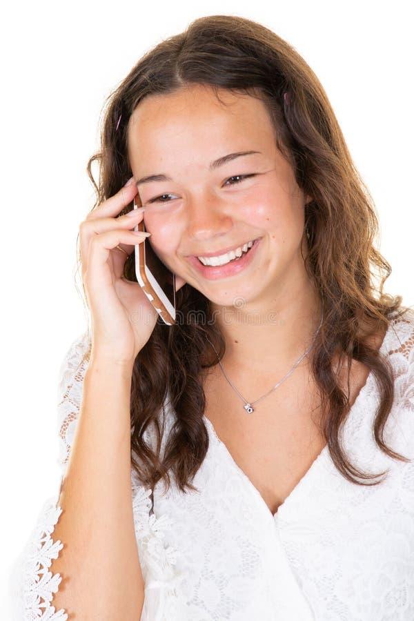 Schöne Frau des jungen jugendlich, die auf Handystellung nahe weißer Wand spricht stockfoto