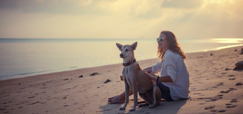 Schöne Frau des jungen Mädchens, die auf dem Strand im Sand mit ihrem Hund sitzt und den schönen Sonnenuntergang aufpasst lizenzfreie stockbilder