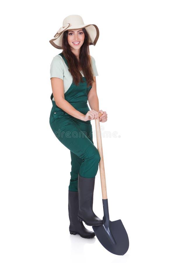 Schöne Frau, die Anlage und Gartenarbeit-Schaufel anhält lizenzfreies stockfoto