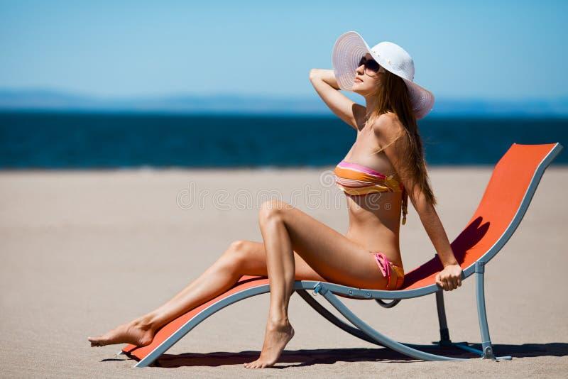 Schöne Frau, die auf einem deckchair am Strand liegt lizenzfreie stockfotografie