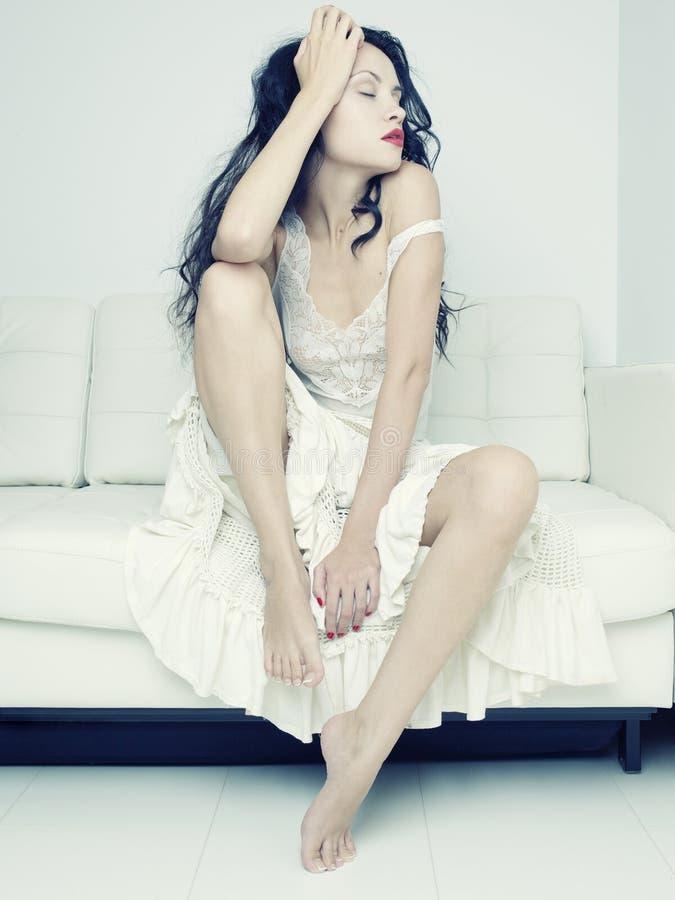Schöne Frau, die auf einem Sofa sitzt lizenzfreies stockfoto