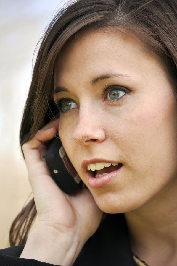 Schöne Frau, die auf Handy spricht lizenzfreie stockfotos