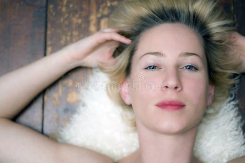 Schöne Frau, die auf Wolldecke liegt stockfotografie