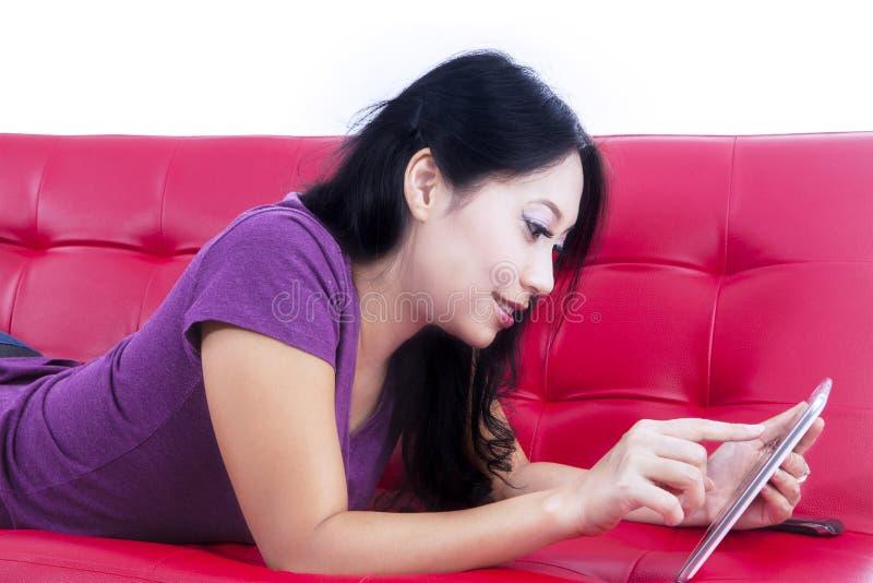 Schöne Frau, die Berührungsfläche auf dem roten Sofa - lokalisiert verwendet